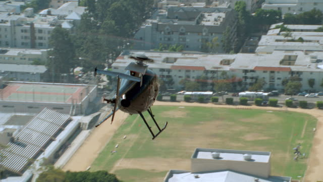 a black helicopter flies over hollywood boulevard in hollywood, california. - helicopter stock videos & royalty-free footage