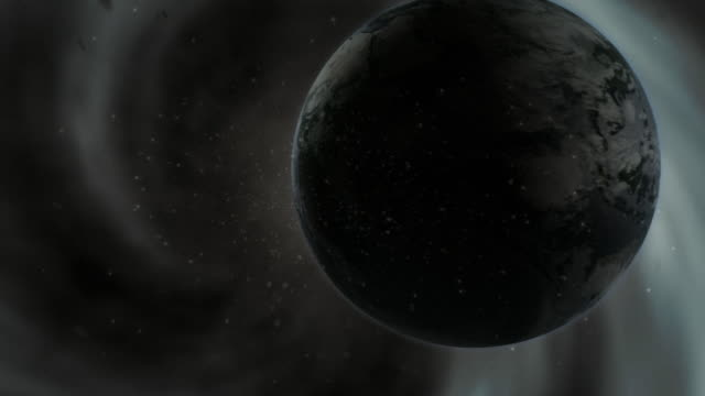 A black hole sucks the Earth in with other debris as it all implodes.