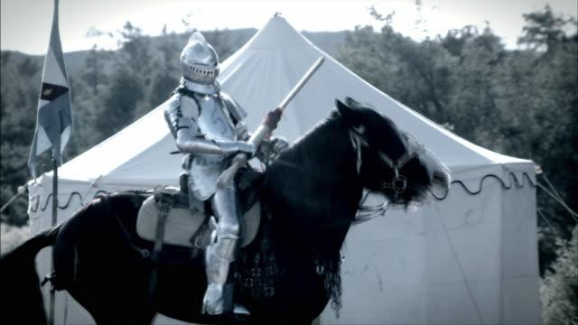 A black horse bucks a knight in shining armor near a white tent.