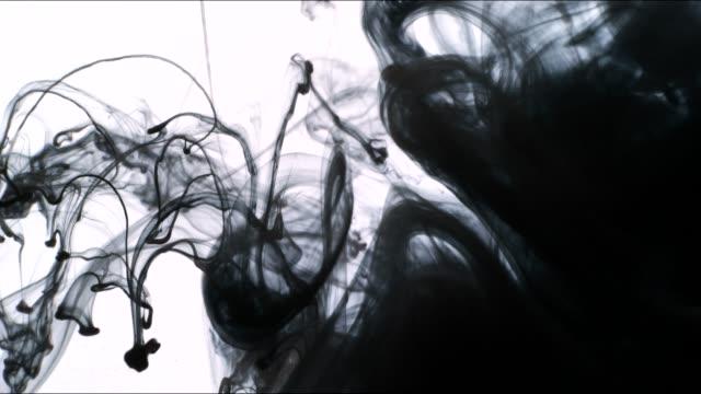 vidéos et rushes de gouttes d'encre noire élargir et tourbillonnent dans l'eau. - touche de couleur