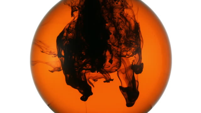 black ink flowing down and swirling under orange colored water in a sphere, becoming darker colored at the end - stationary stock videos & royalty-free footage