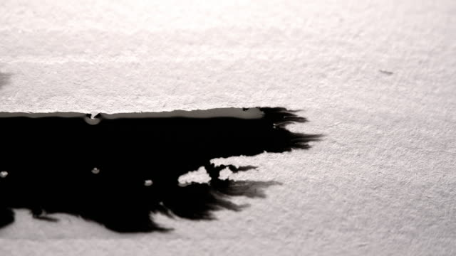 Black ink run and bleeding in white paper. Ideal ink texture to add to modern projects