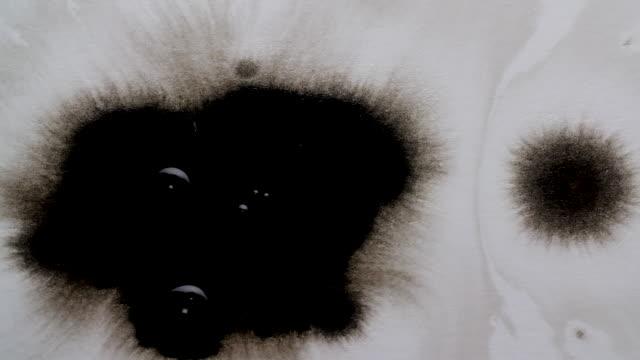 black ink splashing on to white background - black colour stock videos & royalty-free footage