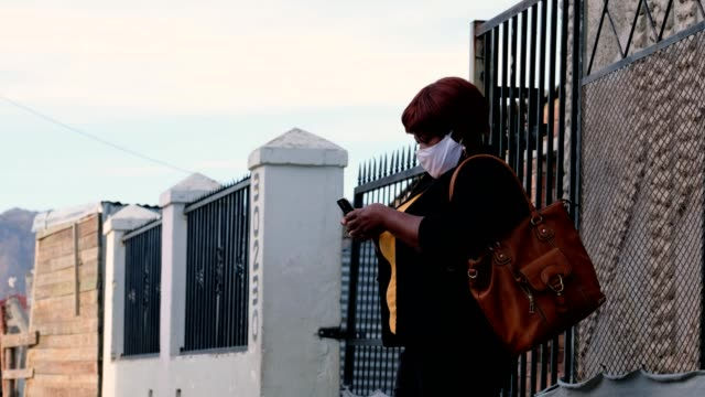 black lady in the street with a facemask using her mobile phone - obscured face stock videos & royalty-free footage