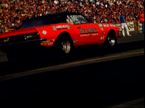 black late 1960s model amc amx super stock car pulling from waiting area steering to camera turning at supernationals at ontario motor speedway /... - 1960 1969 stock-videos und b-roll-filmmaterial