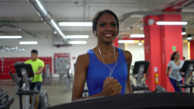 black latin american woman at the gym running on the treadmill - headphones stock videos & royalty-free footage