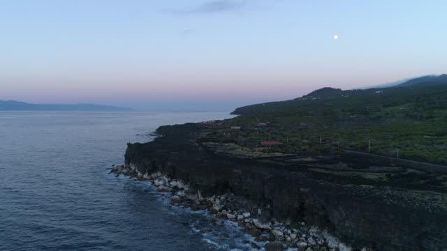 black lava coastline aerial with full moon - アゾレス諸島点の映像素材/bロール