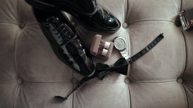 black leather shoes, wrist watch, bow tie and cuff links on sofa - fashion collection stock videos & royalty-free footage