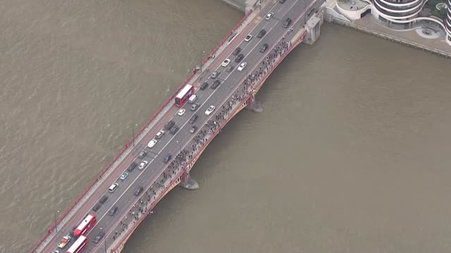 aerials of central london protests england london black lives matter protesters march past mi6 building and over vauxhall bridge / - central london video stock e b–roll