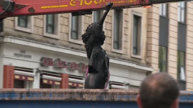 bristol state that replaced edward colston's removed; england: bristol: ext various of statue of black lives matter protester placed on plinth that... - statue stock videos & royalty-free footage