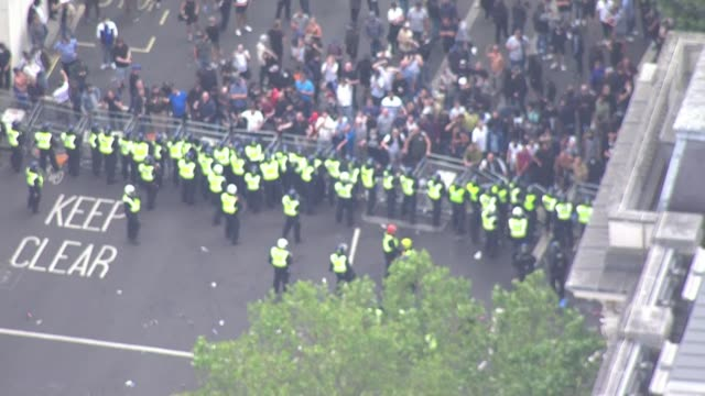 aerials protesters clashing with police in westminster england london westminster police barricade on whitehall pulling down crowd control barriers - war and conflict stock-videos und b-roll-filmmaterial
