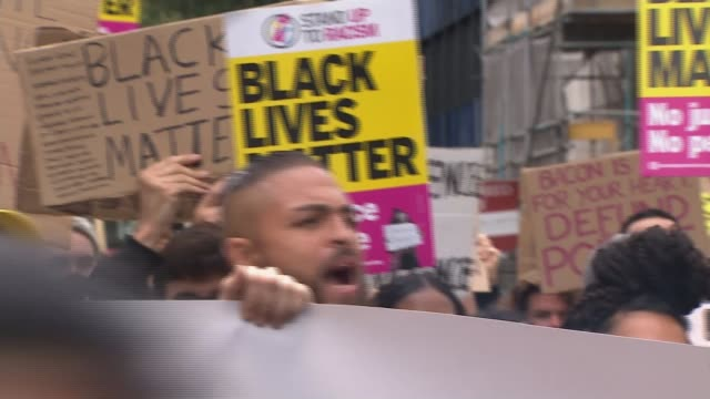 demonstrators gather for 'peace march' against racism; england: london: notting hill: ext protesters sitting in the road demonstrators marching along... - racism stock videos & royalty-free footage