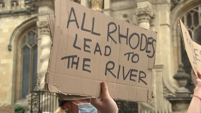 protest against oriel college cecil rhodes statue; england: oxfordshire: oxford: ext sheet on ground 'post colonial studies matter' as person sings... - oxford england stock videos & royalty-free footage