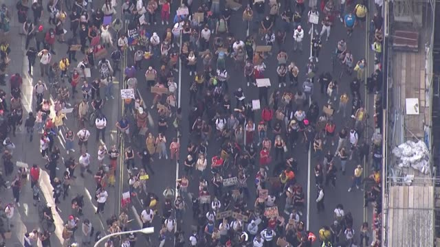 protest march through london: air views; england: london: ext air views zoom in demonstrators along reflection of demonstrators in windows of glass... - group of people stock videos & royalty-free footage