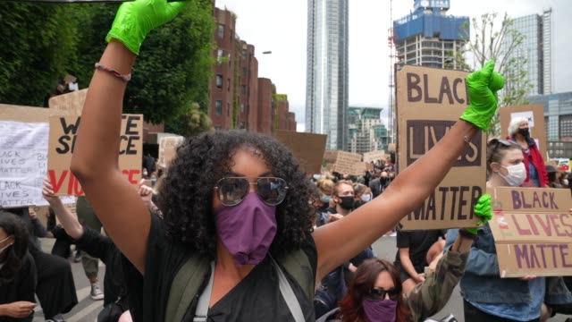 vidéos et rushes de black lives matter protester holds a fist in the air outside the american embassy in london on june 7 2020 in london united kingdom the death of an... - fist