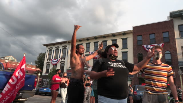 """black lives matter protester who was punched, and is bleeding, flips off bikers, and others during the red, white, blue rally to """"defend the police""""... - white点の映像素材/bロール"""