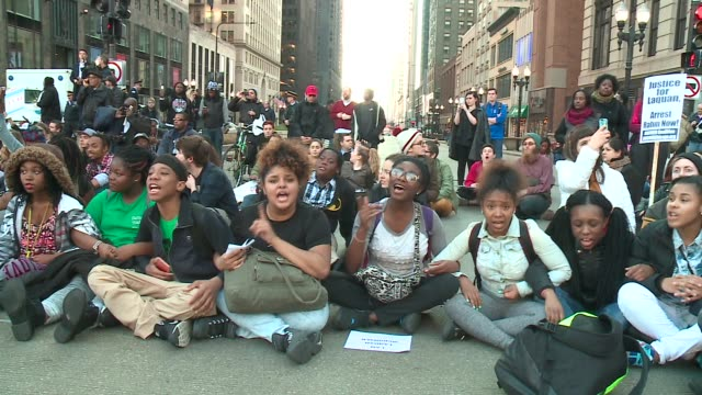 stockvideo's en b-roll-footage met wgn 'black lives matter' protesters sitting in the street marching downtown demanding mayor rahm emanuel and other city leaders resign in chicago on... - black lives matter