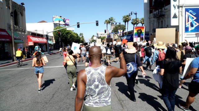 vidéos et rushes de black lives matter protestor raises his fist as he marches down hollywood boulevard during a black lives matter protest in memorial of george floyd,... - hollywood california