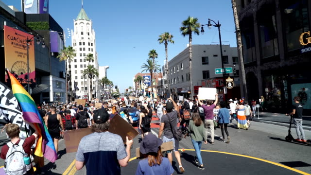 black lives matter protestors march down hollywood boulevard holding signs for social justice, during a black lives matter protest in memorial of... - social justice concept 個影片檔及 b 捲影像