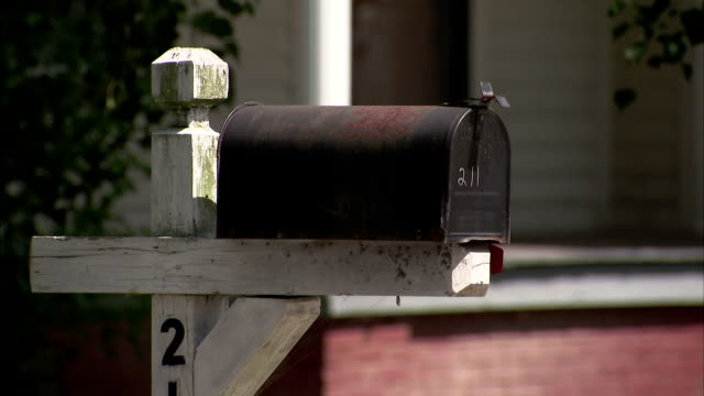A black mailbox sits on a white post. Available in HD.
