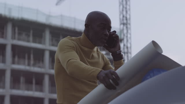 black male architect looking at blue prints at construction site and talking on phone to engineer - one mature man only stock videos & royalty-free footage