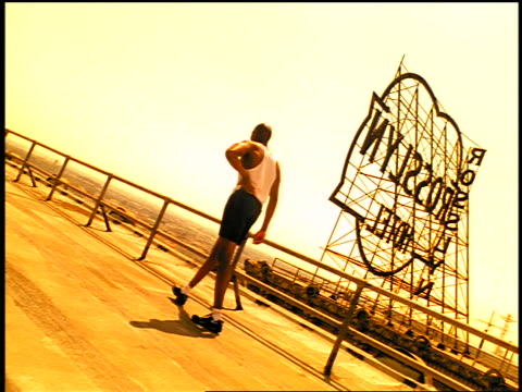 sepia black male athlete walking on roof of building near large sign - getönt stock-videos und b-roll-filmmaterial