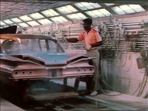 vídeos de stock e filmes b-roll de 1959 black male auto worker spraying blue paint on car body on assembly line / 1960 chevy - 1950 1959