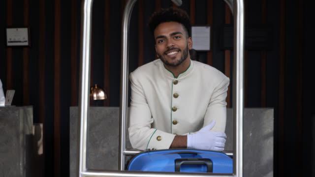 vídeos y material grabado en eventos de stock de negro botones hombre apoyado en el carro de equipaje mientras sonriendo a pie de cámara en el vestíbulo - hospitalidad