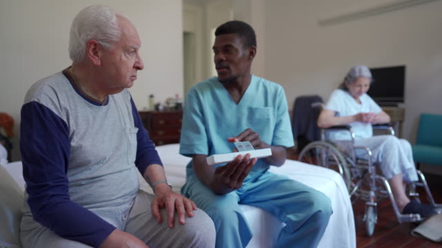 black male caretaker talking to elder man patient - support stock videos & royalty-free footage