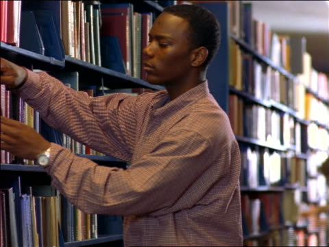 Black male college student pulling + examining book from bookshelf in school library / Boston, MA