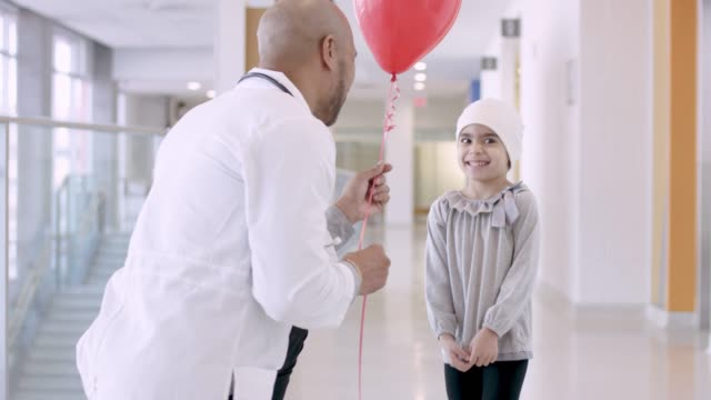 black male doctor giving balloon to child cancer patient - recovery stock videos & royalty-free footage