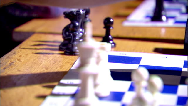 black male hand fingers moving unidentified chess piece up out of frame pressing timer clock resting hand on table behind board - chess piece stock videos & royalty-free footage