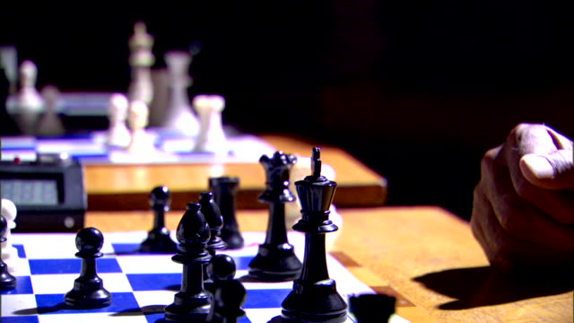 stockvideo's en b-roll-footage met black male hand moving chess piece out of frame making another move returning hand to table holding white bishop moving rook hitting clock - schaakstuk