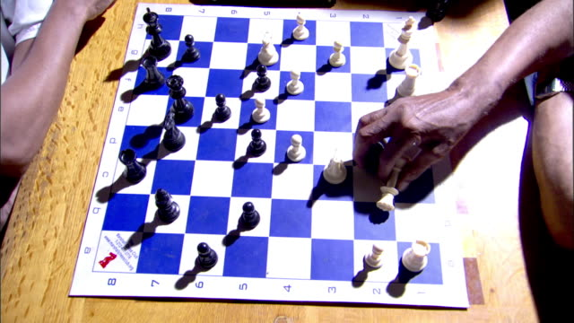 black male hand moving white chess piece touching timer clock out of frame returning black hand w/ captured rook placing w/ other game pieces - chess piece stock videos & royalty-free footage
