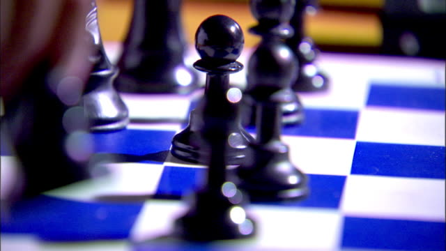 black male hand moving white queen piece out of frame returning to rest hand behind board - chess piece stock videos & royalty-free footage