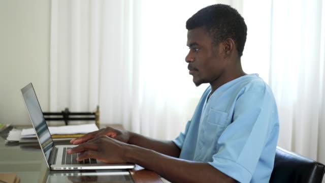 vidéos et rushes de infirmière mâle noire dans des gommages médicaux utilisant l'ordinateur portatif sur le lieu de travail - infirmier