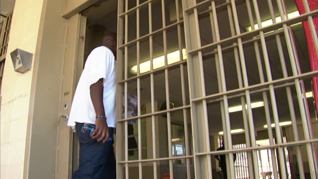 black male prisoner walking through automatic opening sliding gate into prison barred bars incarceration incarcerated not jail correctional facility - louisiana stock-videos und b-roll-filmmaterial