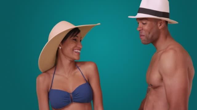 a black man and woman in bathing suits flirt on a blue background - badbyxor bildbanksvideor och videomaterial från bakom kulisserna