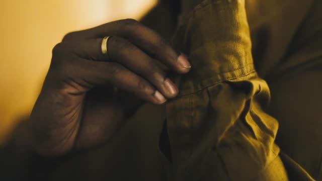 Black man buttoning up his shirt