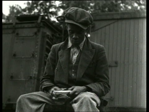B/W black man carving piece of wood near train / Depression / SOUND