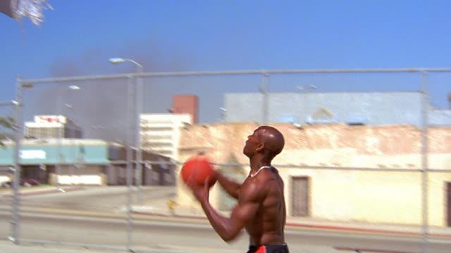 vídeos y material grabado en eventos de stock de ms pan profile black man dunking basketball in outdoor court / los angeles - mate técnica de vídeo