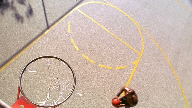 overhead black man dunking basketball on outdoor court / los angeles - sheppard132点の映像素材/bロール