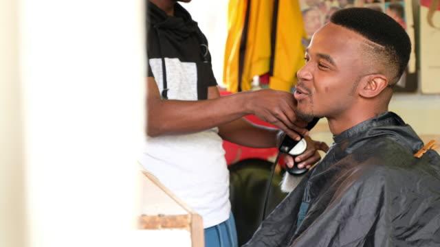 black man enjoys his hair cut at the barber - barber stock videos & royalty-free footage