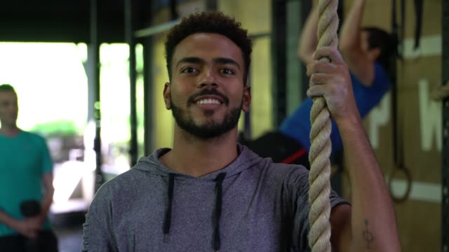 black man finishing after climbing a rope at the gym facing camera smiling - climbing rope stock videos & royalty-free footage