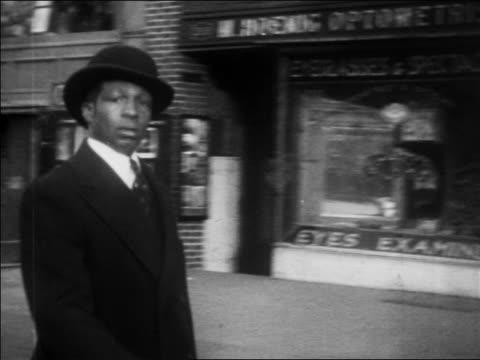 vidéos et rushes de b/w 1930 pan black man in derby walking by camera on harlem sidewalk / nyc / newsreel - afro américain