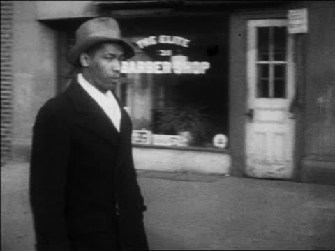 b/w 1930 pan black man in hat walking by camera on harlem sidewalk / nyc / newsreel - harlem stock videos & royalty-free footage