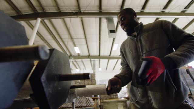 vídeos y material grabado en eventos de stock de un hombre negro en sus veinte años con una barba gira y aprieta un tapón negro en una planta de fabricación - ajustar