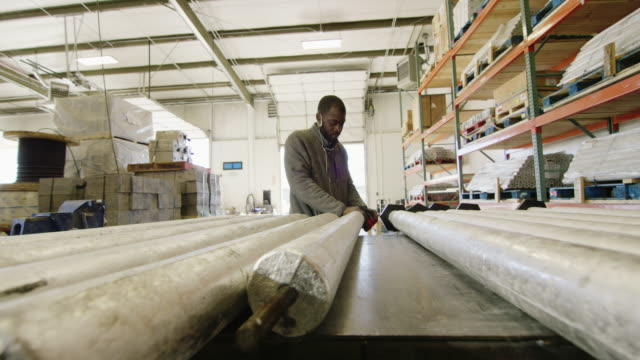a black man in his twenties with a beard rotates and tightens a black end cap on a metal anode in a manufacturing facility - rod stock videos and b-roll footage