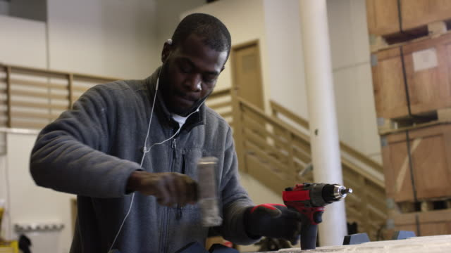 A Black Man in His Twenties with a Beard Rotates and Tightens a Black End Cap in a Manufacturing Facility with a Power Drill in the Foreground