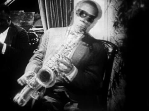 b/w 1928 black man in sunglasses playing saxophone in nightclub / newsreel - 1928 stock videos & royalty-free footage